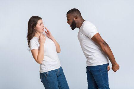 Psychologisch misbruik. Boze zwarte man die emotioneel tegen zijn bange vriendin schreeuwt, haar de schuld geeft van alles, lichte achtergrond met vrije ruimte