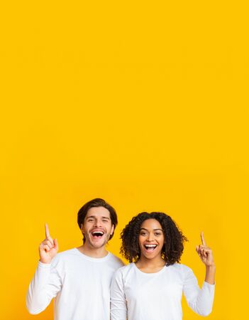 Nice Promo. Interracial couple pointing upwards at copy space and looking at camera, standing together over yellow background Stock Photo