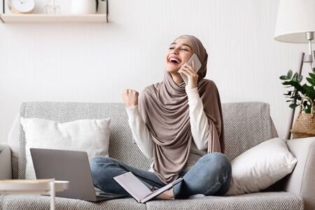 Good news on phone. Cheerful arabic woman in hijab talking on cellphone and celebrating success, she got job, sitiing on couch at home
