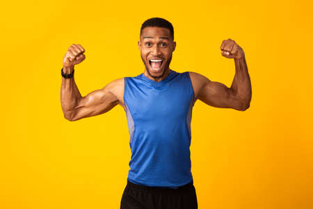Winner. Excited black sportsman celebrating triumph, raising clenched fists in the air isolated yellow studio background