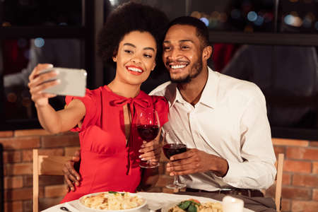 Valentines Selfie. Happy African American Couple Making Self-Portrait On Smartphone Holding Wine Glasses Having Date In Restaurant