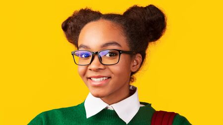 Teenage Headshot. Close up portrait of smiling afro girl in eyeglasses looking at camera over yellow studio wall