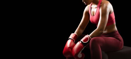 Female boxing concept. Cropped photo of female african boxer before fight, sitting on puff over black background, panorama with free space