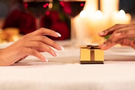Romantic Proposal Concept. Closeup Of Male Hands Pushing Wrapped Gift Ring Box To Girlfriends Hand On Served Restaurant Table. Cropped