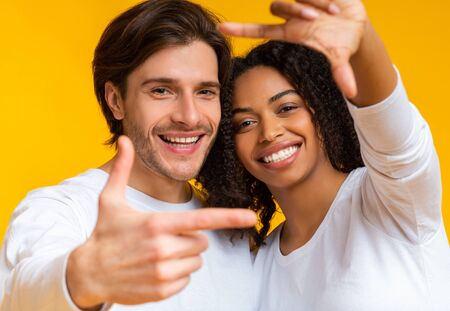 Capturing Happy Moment. Romantic Multiracial Couple Framing Their Faces With Fingers nd Sincerely Laughing, Posing Together On Yellow Background