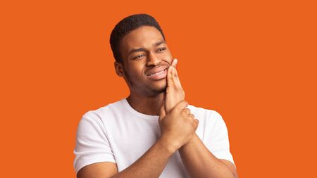 Tooth Pain And Dentistry. Black guy suffering from terrible toothache, touching cheek with hand, panorama