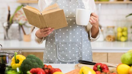 Girl searching for recipe in cookbook and drinking coffee, standing near table with fruits and vegetables, crop
