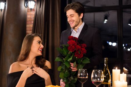 Happy Valentines Day. Enamored man presenting luxury bouquet for his date, free space
