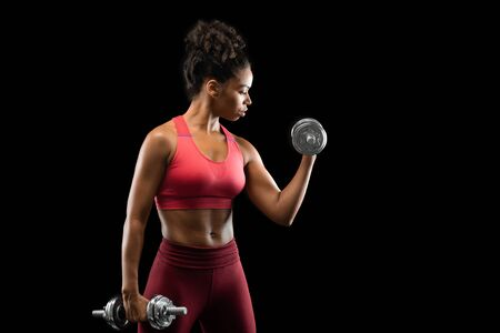 Young afro girl in sportswear pumping iron over black background, free space