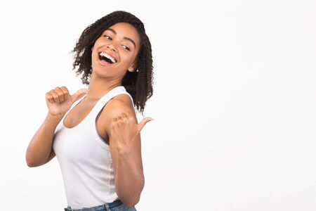 Best Choice. Excited black woman looking and pointing back at copy space with thumbs up isolated over white studio wall Archivio Fotografico