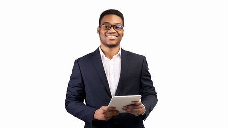 Online Education. Smiling afro man holding digital tablet and looking at camera over white studio background, copyspace Stock Photo