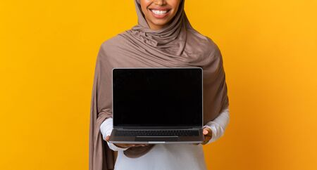 Laptop with blank black screen in hands of unrecognizable afro muslim girl in hijab, standing over yellow background, panorama with free space, crop