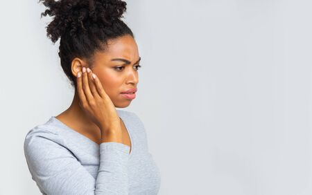 African girl suffering from otitis, rubbing her inflamated ear over grey background, ear diseases concept Zdjęcie Seryjne