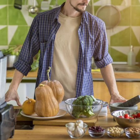 Unrecognizable young man preparing vegetables for cooking healthy salad or food in the kitchen