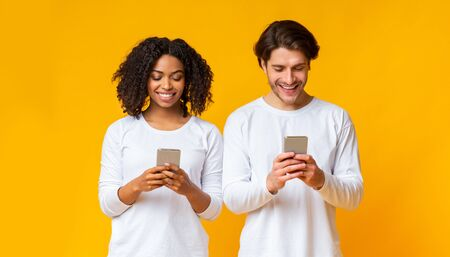 Gadget addiction. Smiling interracial couple busy with their smartphones, looking at device screen and ignoring each other, yellow background
