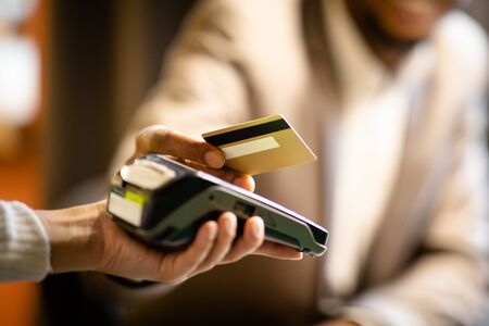 Unrecognizable afro businessman in suit giving credit card to barman paying with gold credit card in cafe, close up