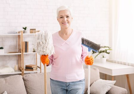Everyday home cleaning. Senior lady holding mop and broom and smiling, free space