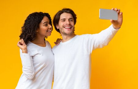 Say Cheese. Cheerful interracial couple taking sellfie on smartphone together, posing over yellow background with free space Stock Photo