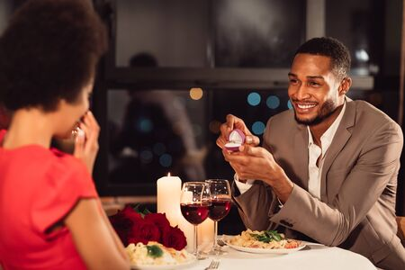 Marry me. Loving afro man proposing to girlfriend holding engagement wedding ring dating in fancy restaurant. Selective focus