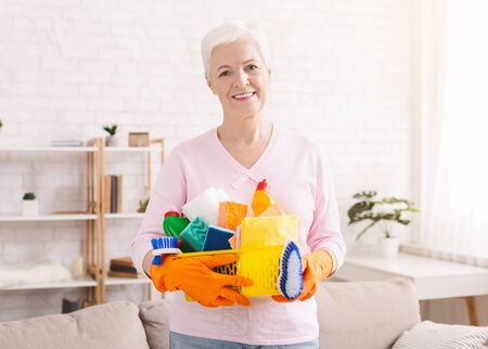 Spring cleaning. Smiling senior lady holding lots of detergents at home, free space