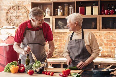 Buona pensione. Coppia senior allegra che cucina insieme un pranzo sano a casa cucina