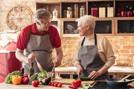 Feliz retiro. Pareja senior alegre cocinando un almuerzo saludable juntos en la cocina de casa