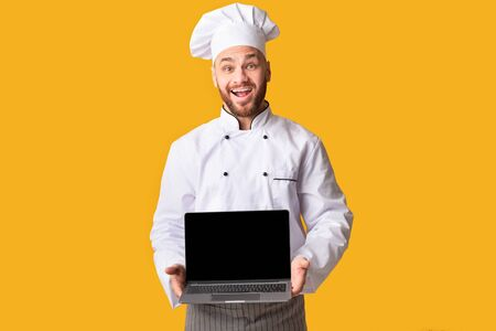 Cooking Food Website. Happy Chef Man Holding Laptop Computer Showing Blank Screen Posing On Yellow Background. Studio Shot Foto de archivo - 138299724