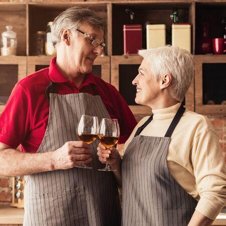 Anniversary. Senior couple clinking with wine glasses at kitchen Foto de archivo - 138299599