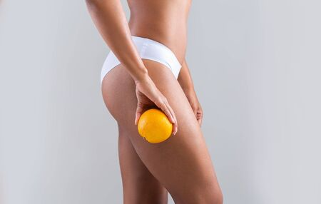 Cropped of black girl holding orange next to her slim legs, cellulite concept