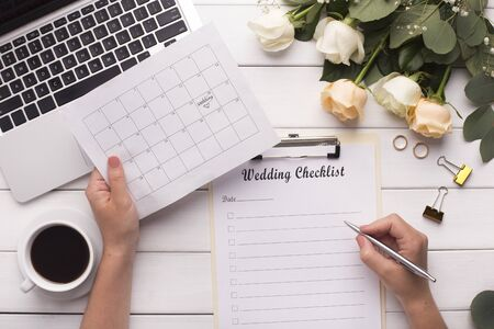 Bride Planning wedding writing checklist and choosing date in calendar, wooden background with cream colored roses and laptop Banco de Imagens