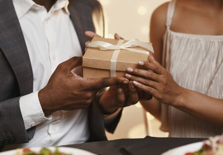 Valentine's surprise. Cropped of african man and woman holding gift box, having dinner at restaurant