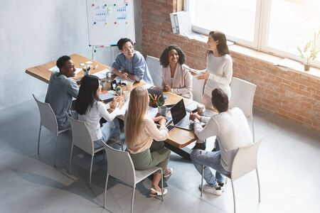 Enthusiastic girl sharing her ideas with cheerful multiracial colleagues while meeting in office, high angle view 版權商用圖片 - 138298310