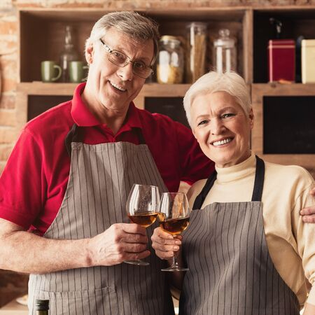 Love for all ages. Happy senior beloved man and woman enjoying wine at kitchen