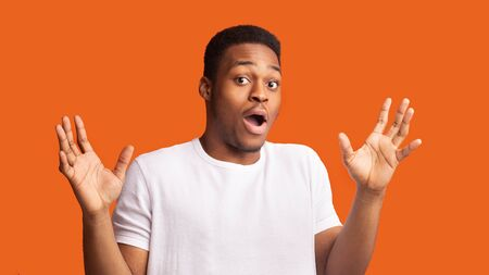 Its Not Me. Confused black man raising his hands and looking at camera, orange studio wall, copyspace, panorama