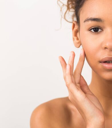 Face lifting concept. Woman touching soft skin on her cheek over light background, crop