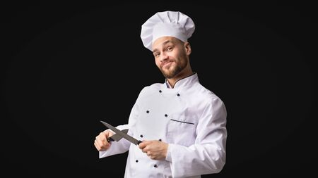 Funny Chef Man Sharpening Knives Standing Over Black Background. Cooking Food. Studio Shot, Panorama