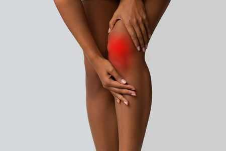 Cropped of afro woman touching her injured knee, suffering from pain in knee