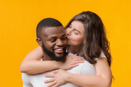 Romantic Moments. Loving Woman Kissing And Hugging Her Afro Boyfriend From Behind