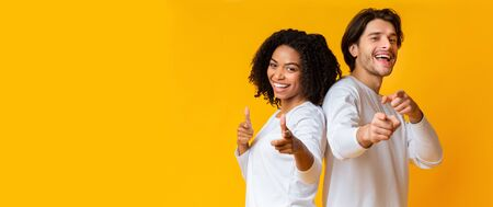 Happy interracial couple pointing at camera with both hands and laughing, posing together over yellow background, panorama with empty space Stock Photo