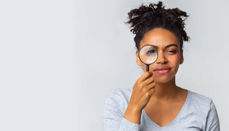 Curious black girl holding magnifier over grey background, panorama with copy space