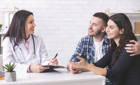 Family consultation. Young couple at doctors appointment at clinic, panorama, free space