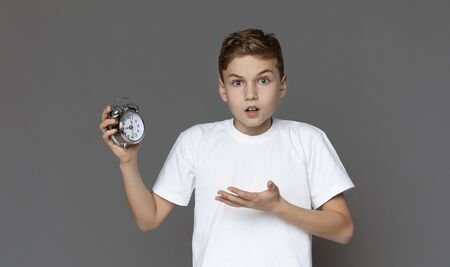 Education and time concept. Shocked teen boy holding alarm clock in hand, grey panorama background