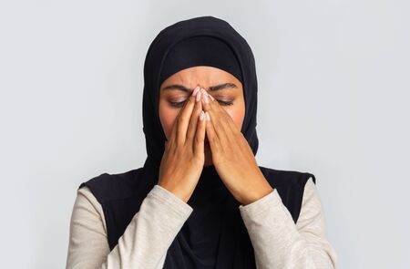 Upset black muslim woman in hijab covering face with hands, cant believe news, depressed and in despair. Light background with copy space