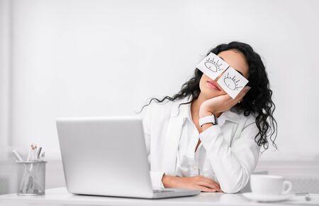 Insomnie. Fille d'employé de bureau improductif paresseux portant des notes autocollantes drôles sur ses yeux dormant sur le lieu de travail, copyspace