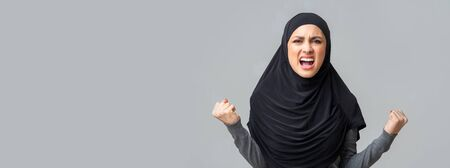 Screaming, hate and rage concept. Angry emotional muslim woman in hijab shouting in fury over grey studio background, panorama with free space