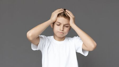 Failure. Upset teen boy holding head in despair, grey panorama background Reklamní fotografie