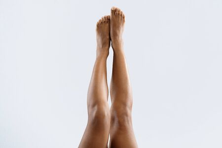 Beautiful black woman lifting her legs up in air, grey background, cropped