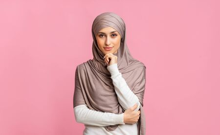 Modern muslim woman. Portrait of confident islamic girl in hijab touching her chin and looking at camera, pink background with free space