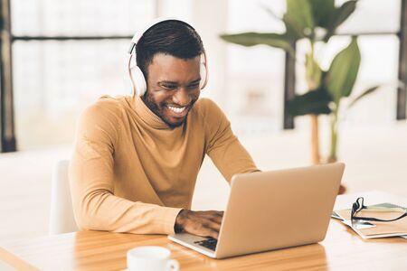 Descanso. Estudiante negro feliz en auriculares viendo videos en línea, charlando con amigos. Copia espacio