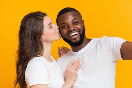 Romantic girl kissing her happy boyfriend while posing for selfie together over yellow background